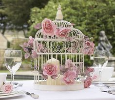 Maybe for side tables/guest book table?    Beautiful wedding centerpiece: wire bird cage with flowers.