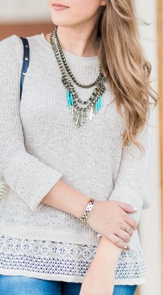 Cream sweater with lace ruffle, destroyed denim jeans, navy crossbody bag, and antiqued gold and turquoise statement necklace styled by blogger Ashley Brooke Nicholas. Click through this pin to see this cute fall outfit idea + learn where to buy each item