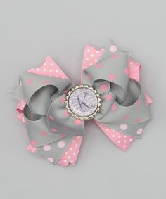 This bow adds personality and pizzazz to hair with its rich color and bubbly patterns. A durable alligator clip base is decorated with layers of heat-sealed grosgrain ribbon and a customized bottle cap.Personalize with initial5'' W x 4'' HGrosgrain ribbon / metalMade in the USA