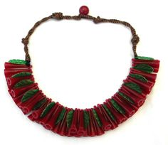 This vintage 1930s necklace features a tassel of garnet horn-shaped and emerald leaf celluloid beads with smoky topaz silk cord. There is a single round garnet bead designed as part of the clasp. The necklace is not marked; however, it is reminiscent of early Frank Hess for Miriam Haskell jewelry in material and design.