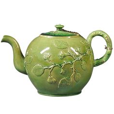 A Large Staffordshire Green Glazed Punch or Tea Pot, circa 1770 |A large Staffordshire green glazed earthenware punch or tea pot and cover, attached with a small chain, English, circa 1770, of globular form with molded crabstock, branch-like handle, the body decorated with applied flowers, foliage, and vines in relief.