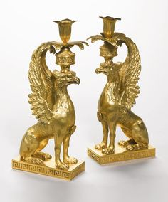 A pair of George III ormolu candlesticks, attributed to Diederich Anderson, after a design by William Chambers circa 1765 in the form of a chimera supporting a flower cast candle-holder and drip-pan on its head, the breast set with an oval medallion and on a plinth base with sectionalised Greek key pattern decoration, possibly with chains missing to medallions, the tails missing