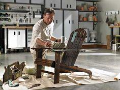 Armoires Gladiator®, panneaux GearWall®, crochets, tablettes en métal, accessoires et établi avec armoires modulaires glissées en dessous. Homme peignant une chaise en bois.