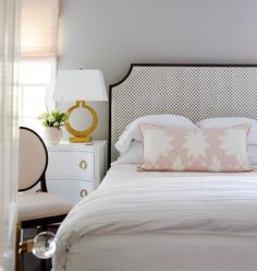 A black and white polka dot headboard framed with black wood trim accents a bed dressed in a pink lumbar pillow placed next to a white curved nightstand adorned with brass ring pulls and a gold lamp, Ring Form Lamp, placed under a window covered in a blush pink roman shade.
