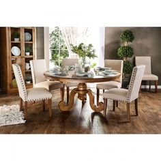 "Who says you can't have a spacious dining space with a round table? This over sized dining table features a table top 63"" in diameter, enough to seat six of your family and friends. The unique pedestal base has intricate curved legs and fine turned details, while the matching chairs with nailheads and upholstered in ivory fabric bring out the charm of the oak finished wood, which is made of heavy, solid pine."