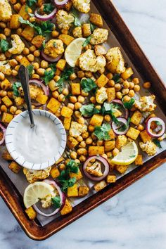 Sheet Pan Chickpea Tikka- roasted cauliflower, potatoes and chickpeas are tossed with Indian spices and served with a cooling ginger-garlic and lemon yogurt sauce. Simple to make and clean-up is a breeze! (vegan, gluten-free, grain-free)