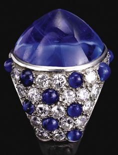 An Art Deco cabochon sapphire and diamond ring, probably by Cartier, circa 1930. The circular cabochon sapphire collet-set to a surround of circular-cut diamonds decorated with cabochon sapphires, mounted in platinum, French assay and indistinct maker's marks. #Cartier #ArtDeco #ring