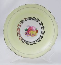 Beautiful tea cup and saucer by Paragon. Tea cup and saucer are yellow with flowers. Silver trimming on cup and saucer edges. Set is in excellent condition (see photos). Markings read: Paragon By Appointment To H.M. The Queen and H.M. Queen Mary Fine Bone China England Regd Paragon