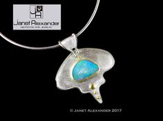 Argentium sterling silver with 22k gold bezel and granulation. The stone is an opal and hangs on an Omega chain.