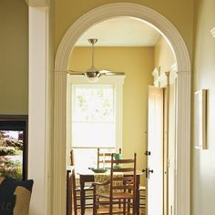 New arched doorways with vintage Victorian detail frame a wider entrance from the hall to the kitchen.