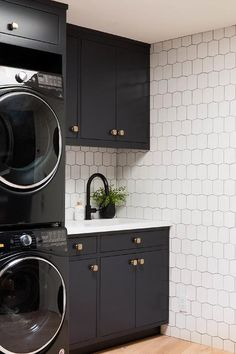 Stacked black front-loading washers and dryers are enclosed beneath a black overhead cabinet and beside black flat front cabinets adorned with brass square knobs and a white quartz countertop. White Laundry Rooms, Mudroom Laundry Room, Modern Laundry Rooms, Laundry Room Layouts, Laundry Room Remodel, Laundry Room Cabinets, Laundry In Bathroom, Small Laundry Sink, Laundry Room Appliances