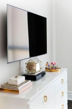 Love this glam white lacquered bedroom dresser with brass hardware and ring drawer pulls, paired with metallic gold catchall trays and objects, with the shiny wall-mounted flatscreen TV above. Such a great way to style a room or vignette around a TV -- treat it like a piece of art and frame it with symmetry for a beautiful affect!