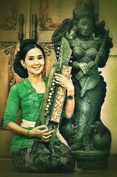 Bali's world music diva Ayu Laksmi with her new favourite music maker, a traditional Balinese string instrument, the penting #musik #Bali #green