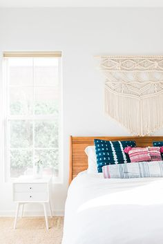 White bedroom with bright pillows and macrame wall hanging.
