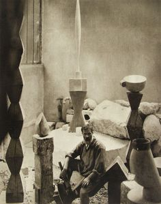 "Photo of Brancusi in his studio – a version of ""Bird in Space"" in the background. A version of ""Endless Column"" to the left."