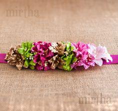 Consigue el cinturón de flores más especial con este complemento formado por lirios de papel rosas, fucsia, verdes y dorados.