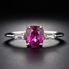 A luscious, deeply saturated hot raspberry pink cushion-cut sapphire is traditionally presented between a shimmering pair of tapered baguette diamonds. This enchanting and mesmerizing gemstone radiates from within an 18 karat yellow gold setting and atop 18k white gold ring shank.