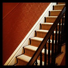 Darkened the floors and railing and added a natural fiber seagrass up the stairs. The paint is Farrow & Ball Paint No.247 Terre D'Egypte - a deliciously warm red-brown terracotta on textured wallpaper.