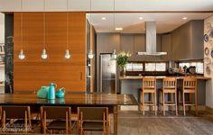 """Quando a porta de cumaru (3,65 m de largura) se abre, é a vez de a proprietária entrar em ação. """"Adoro a família por perto enquanto preparo o jantar"""", diz. Na mesma cor da tinta do balcão, os armários da cozinha receberam Formica grafto (cód. L0 13). Projeto de Sandra Sayeg"""