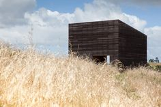 Cheshire Architects' blackened timber cabins overlook the sea