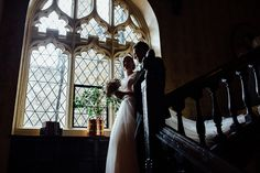 Documentary Kent wedding photography of a bride and her father coming down the stairs at Eastwell Manor
