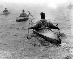 Eskimos launching kayaks through the surf of the Bering Sea, Alaska.
