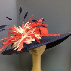 Beautiful navy derby hat with red and white accent feathers.