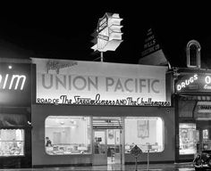 """I must admit, I do enjoy a night shot of a building that has been thoughtfully lit. This is the sales office of the Union Pacific railway at 140 Pine Ave, Long Beach, circa 1940s. I love the font they used for """"Road of The Streamliners and The Challengers"""" (which were types of locomotives.) I also find it interesting that they presented themselves as """"The Progressive Union Pacific"""" – it appeared on a lot of their ads, too."""