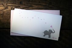 Tell em you love em all year round with this adorable Baby Elephant Card! This card makes a lovely valentine, but is also a beautiful card for any time of year! Each card features a grey baby elephant running across the front blowing pink, heart-shaped bubbles with his trunk. The message Love you. is printed on the bottom right-hand corner on the front and the card is blank on the inside for your own personal greeting!  • Card Dimensions: Monarch | 3.5x7.25 • Sustainably letterpress printed…