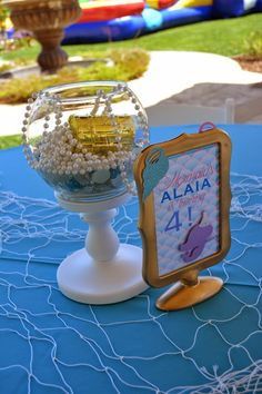 A LITTLE MERMAID party centerpieces with gold treasure box and pearls.