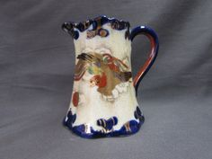 "Vintage Japanese Porcelain Pitcher.  This small porcelain pitcher has rich cobalt blue, rust and gold decor.  It features what looks to be a Phoenix.  The pitcher is marked in Japanese.  It is approx. 4 5/8"" tall x 4"" base x 2 3/4"" opening.  It is in good condition with no chips or cracks.  There is wear and yellowing of the white around the outside of the pitcher."