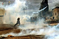 Jan. 13, 2012. Palestinian protesters run to seek cover from tear gas fired by Israeli troops during a weekly protest against the Jewish settlement of Qadomem, near Nablus, the West Bank.