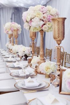 Gold pastels and towering flower arrangements bring light to an indoor reception.