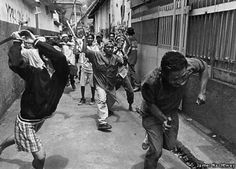 JAMES NACHTWEY, USA, MAGNUM PHOTOS FOR TIME MAGAZINE.  2ND PRIZE STORIES 1999 WORLD PRESS PHOTO.  VICTIM OF MUSLIMS IN PEMBANGUAN 1 DISTRICT IN NORTHERN JAKARTA WHO FOUND THEIR MOSQUE DAMAGED. THE VITIM IS CHASED DOWN AN ALLEY AND KILLED.
