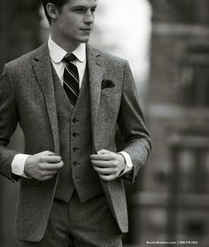 A classy three-piece tweed suit and rounded collar white tailored shirt.