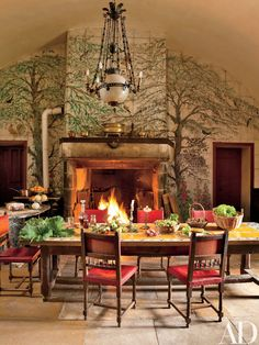 Joy conjured the verdant ceramic tile surrounding the fireplace in the kitchen, where Henri II–style chairs encircle an antique tile-top table.