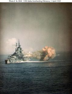USS Idaho BB-42,fires the 14/50 guns of Turret Three at nearly point-blank range, during the bombardment of Okinawa, 1 April 1945.Photographed from USS West Virginia (BB-48). -
