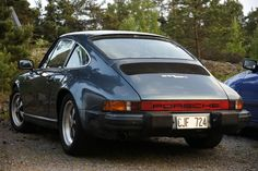 A blur Porsche 911 SC parked in front of some trees
