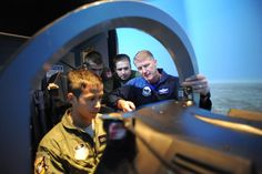 """Before you even get to see an airplane for more than an """"experience flight"""" you go back to school. Dana Gunter (right), 559th Flying Training Squadron T-6 simulator instructor, teaches Air Force Academy Cadets (right to left) Johnathan Fonbuena, Conner McKinney and Arturas Kucharevas how to fly the T-6 simulator on Randolph Air Force Base July 15. (U.S. Air Force photo/Rich McFadden) (released)"""