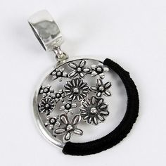 "$10.90 for this newest piece of Scarf Jewelry.  This flower collage pendant scarf jewelry piece is sliver toned. It has a wrap accent of black string coordinated with the black etched floral cluster. It hangs from a simple smooth ring that easily slides on to most scarves.  It measures 3.25 x 2.25""."