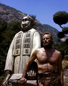 "Charlton Heston in 1968's Planet of the Apes, standing in front of a statue of ""The Lawgiver""..."