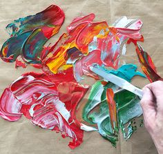 Spreading acrylic paint on a craft sheet for making paint skins