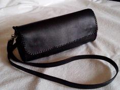 Bolso realizado en piel de color negro , cosido a mano con hilo de cuero, cierre de dos imanes.