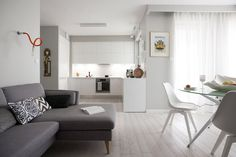 Otwarty aneks kuchenny dyskretnie pozostaje w tle salonu. Z częścią wypoczynkową łączy go jednolita posadzka, szare ściany i kolorowe dodatki w orientalnym stylu. Nad kanapą zainstalowano nowoczesne kinkiety na praktycznym giętkim wysięgniku.