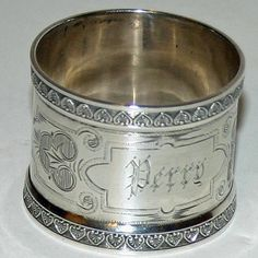 This beautiful sterling napkin ring was made by the noted New York firm of Wood and Hughes and bears their mark, shown in one of the pictures. There