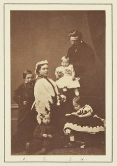 Nov 1865; From left to right: Prince William; the Crown Princess; Prince Henry (sitting on the floor); Prince Sigismund (being held by his father); the Crown Prince (standing behind holding Sigismund); Pss Charlotte (seated on stool looking at book).