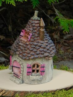 This lovely cottage is sure to be a lovely focal point for your fairy garden or miniature garden. It has a hinged front door with a darling little acorn for a door knob. The door swings open and closed and the cottage is hollow, allowing for a tea light to illuminate the house at night. The light will sine through the three windows, include in the tiny window in the pinecone hinged roof. Cottage is made of resin. ✿ Cottage measures approximately 7 1/2 inches tall x 5 inches wide and dee...