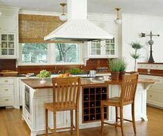 Classic White  An enameled hood looks right at home in a kitchen whose white-painted cabinets join natural-finish wood floors, stools, and countertops. Other traditional elements include schoolhouse-style pendant lights and drawers with bin pulls.