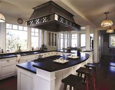 love the two-tiered, black granite countertops, white cabinets, dark wood stools, hood...