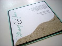 Tiffany's on the Beach wedding invitation by This & That Creations.   Square metallic turquoise blue and flat black invitation with actual sand on the invitation.